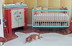 Baby crib painted turquoise blue in a neutral nursery