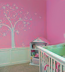 Tree decal stickers mural on the walls of a pink baby girl nursery