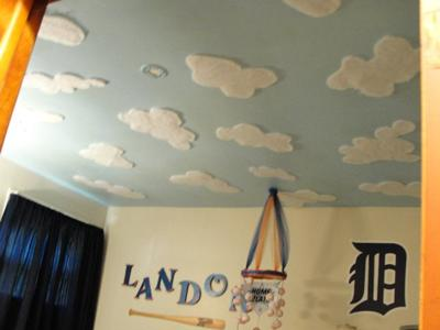Cloud painting on a baby boy's sports nursery ceiling mural