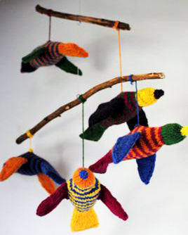 Homemade DIY knit tropical birds for a baby crib mobile in a forest birds theme nursery