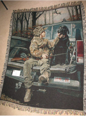 Ducks Unlimited throw blanket featuring a young boy sitting in the back of a truck with his black Labrador hunting dog