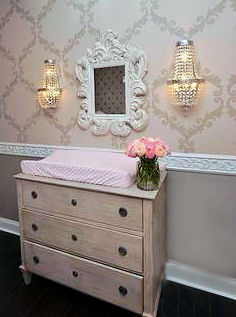 Carved wooden wainscoting trim chair rail in a pink and grey rococo nursery room