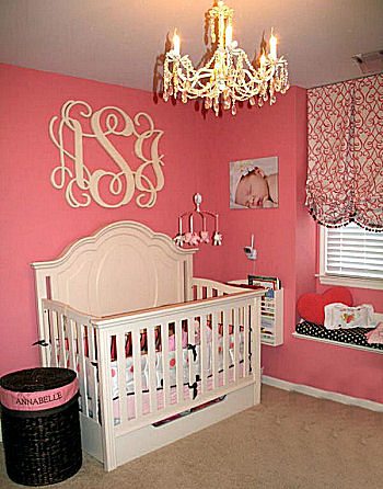 Elegant watermelon pink and black baby girl nursery room with custom wooden wall letters and baby bedding