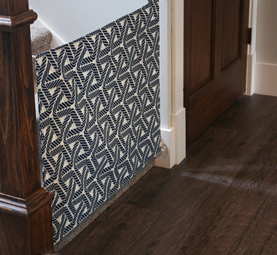 Homemade fabric baby gate made of heavy duty black and white canvas with a modern geometric pattern.