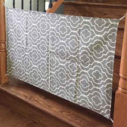 Homemade fabric baby gate made of heavy duty grey and white canvas with a modern geometric pattern.