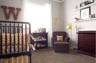 The sitting area in the forest themed nursery is lit by a modern yellow floor lamp and features a wooden, whitetail deer silhouette as a wall decoration.