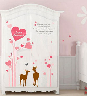 Deer stickers on an armoire in a baby girl nursery room