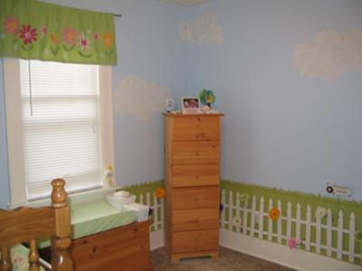 Cloud painting on a baby girl garden nursery wall above a picket fence surrounded by flowers