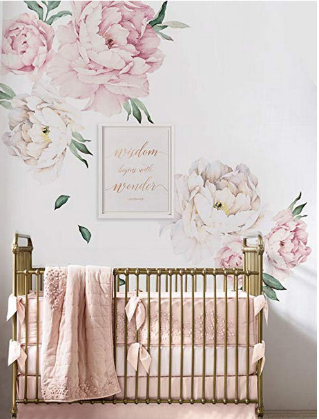 Rose pink white and gold girl nursery room with a gold crib and large floral wall decals and artwork with gold lettering.