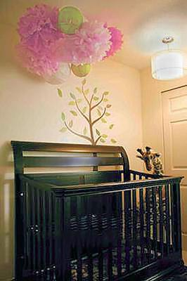 Handmade tissue paper pom pom nursery baby mobile in pink and green hung from the ceiling.