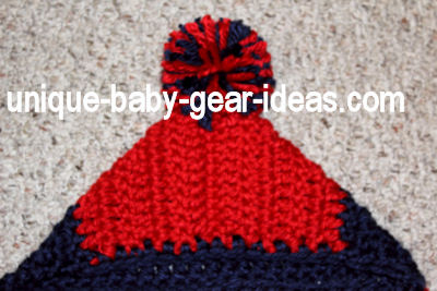 Large pom pom made from thick super chunky red and blue yarn for a crochet hooded baby bunting crochet for a baby Ole Miss fan