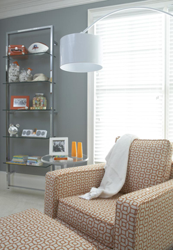 Modern orange and white upholstered nursery chair with a chrome floor lamp
