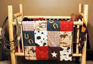 Homemade rustic baby crib made using logs for a baby boy's western cowboy baby nursery theme room.