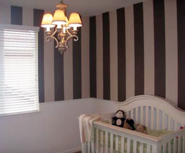 Baby girl nursery room with painted stripes and DIY wainscoting on the wall