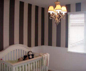 Baby girl nursery room with DIY pink and brown stripes painted on the wall