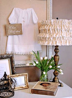 Vintage baby christening gown on display in a shadow box on a nursery wall