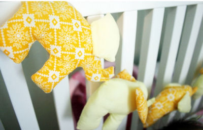 Bright yellow stuffed elephant bunting banner for a baby nursery