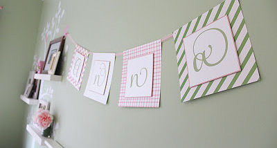 Pink and green paper garland on the nursery wall with letters that spell a baby girl's name