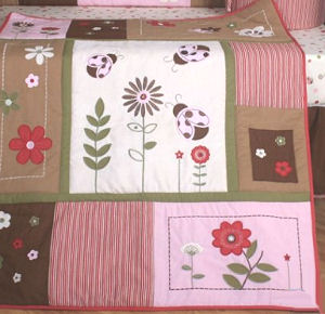 Patchwork baby crib quilt with pink and brown ladybug appliques for the nursery room