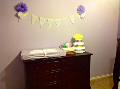 Nursery wall banner over a baby girl's diaper changing station