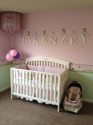Makenzey's name spelled in letters on her pretty pink nursery wall behind her baby crib