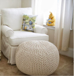 A comfortable nursery chair with a pillow featuring Christopher Robin and Winnie the Pooh