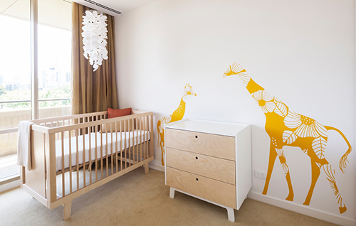 Modern gender neutral giraffe theme baby nursery ideas with large mother and baby giraffe on the wall.