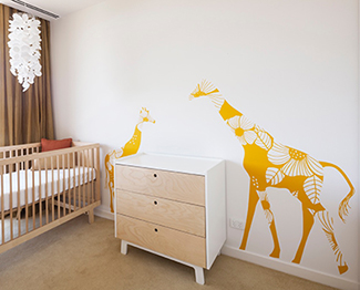 Large mother and baby giraffe nursery wall decals in a modern baby room