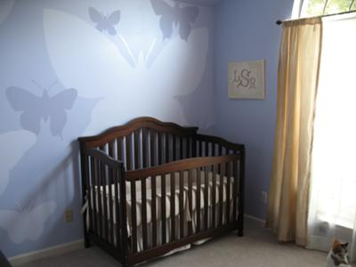 A view of our baby girl's crib, the hand-painted butterflies nursery wall mural in shades of lavender and window treatments.