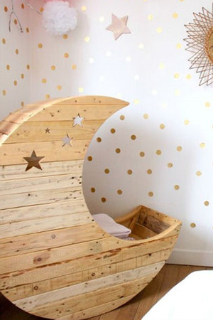 Crescent moon shaped handmade wooden baby cradle with a celestial stars theme for a shabby chic nursery room.
