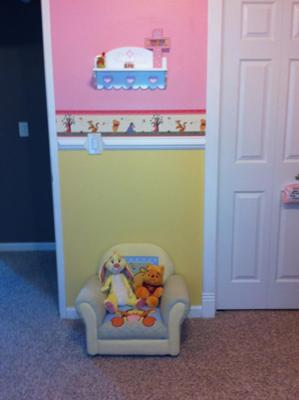 We painted the walls of our baby girl's Winnie the Pooh nursery in pink and yellow paint from Behr and added a white wooden molding as a chair rail to divide the colors.