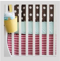 Stripes and polka dots baby crib bedding in a shared nursery