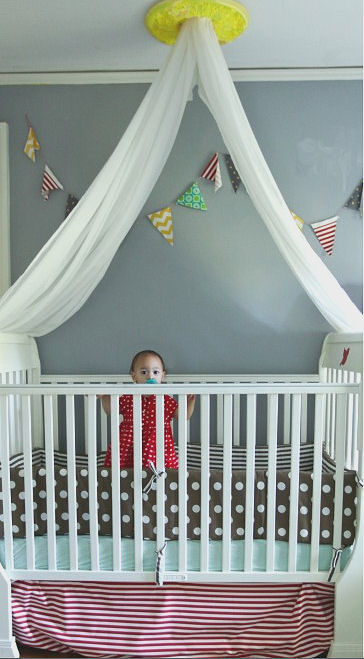 Beautiful baby girl standing in her crib located in a colorful shared nursery with gray walls and a yellow ceiling medallion