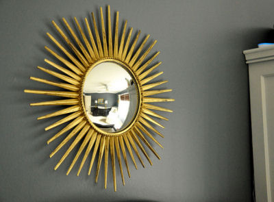 Gold metallic sunburst wall decoration in a navy blue and white baby boy nursery room