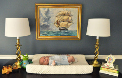 Tall sailing ship print framed in a gold-tone frame in a baby boy's nursery room
