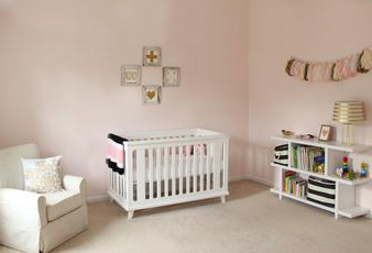 An elegant blush pink baby girl nursery room decorated with metallic gold décor and wall decorations