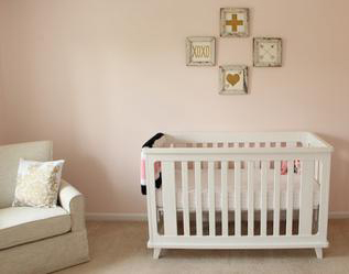 An elegant baby girl nursery room with blush pink wall paint color