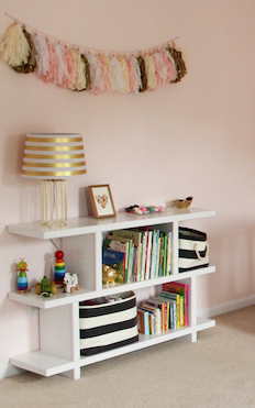Homemade DIY nursery bookshelf and black and white storage bins in a pink baby girl nursery room