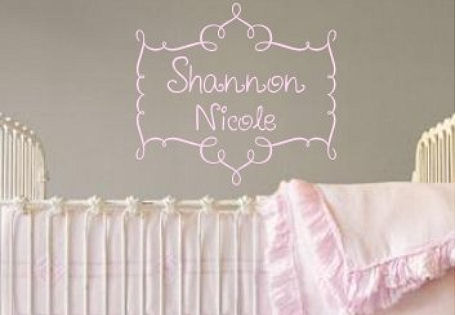 Pink personalized baby girl name decal surrounded with a scroll design on a gray nursery room wall