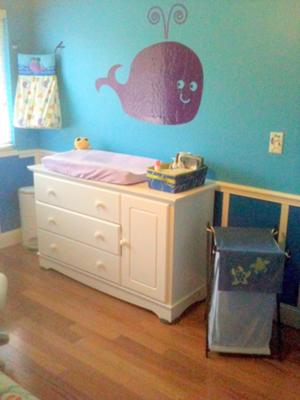 Purple whale nursery wall decal over the baby's changing table dresser combo. Ocean Wonders Diaper Stacker, Sea Babies Hamper