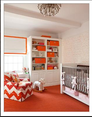 Pink white and orange baby room for a girl with a nursery chair upholstered in orange and white chevron fabric.