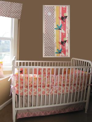 Our baby girl's colorful custom nursery was designed with bedding and nursery decor from the