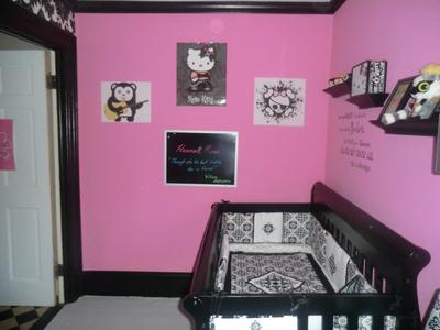 Our baby girl's nursery has a bold hot pink wall paint color that contrasts with the black and white baby crib bedding set and punk nursery theme.