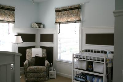 Chocolate brown and blue paisley nursery window valances and baby crib bedding in a baby boy room.