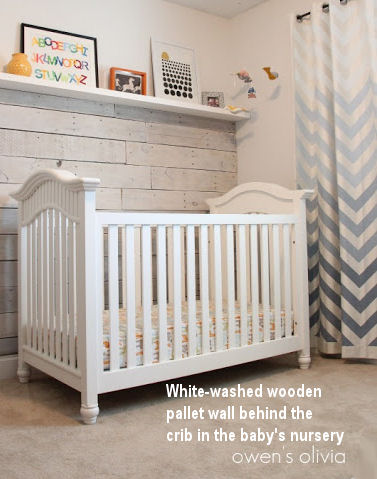 Recycled wooden pallets have been white-washed and used to panel the baby's nursery wall