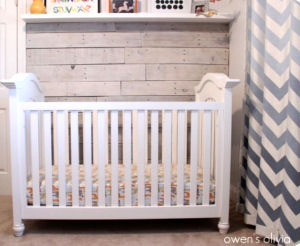 The pallet wall and chevron curtains in this baby boy's nursery would be perfect for a beach cottage theme room