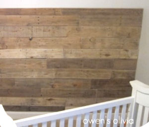 A baby nursery wall paneled with rustic boards from recycled wood pallets