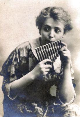 Female actress posing as Peter Pan playing a flute