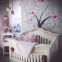 Pink and dark brown baby girl nursery design with pom poms ceiling mobile