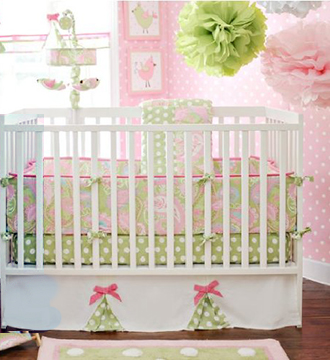 Pink white and lime green baby crib bedding in a baby girl nursery room with tissue paper pompoms